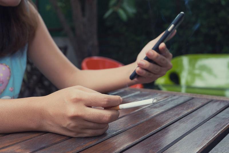 Midsection of woman with cigarette using mobile phone at table