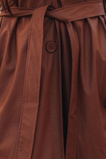 Street style fashion details of autumn trench leather long stylish brown coat. female outfit
