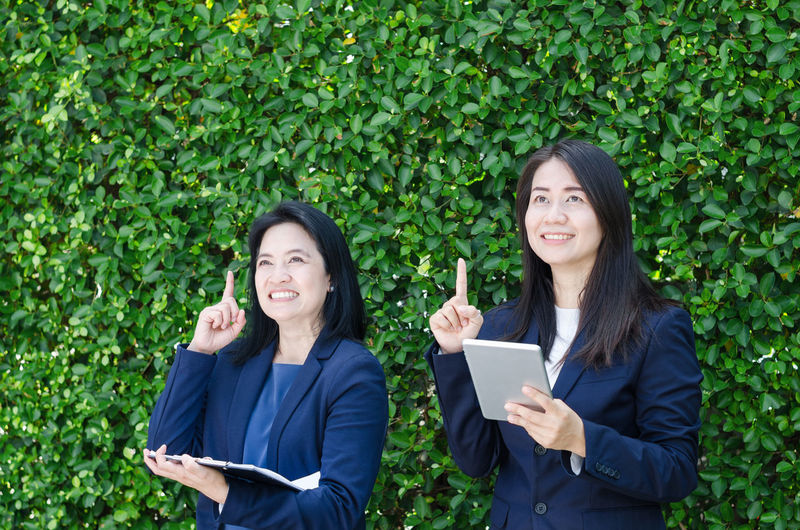 Thoughtful Businesswomen Pointing While Standing Against Plants
