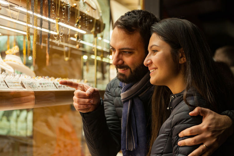Happy beautiful young couple choosing a wedding rings while smiling while doing shopping in Florence. Couple Ponte Vecchio - Firenze Adult Bonding Cheerful Couple - Relationship Day Happiness Indoors  Jewelry Leisure Activity Lifestyles Men Night People Ponte Vecchio Real People Smiling Togetherness Two People Young Men