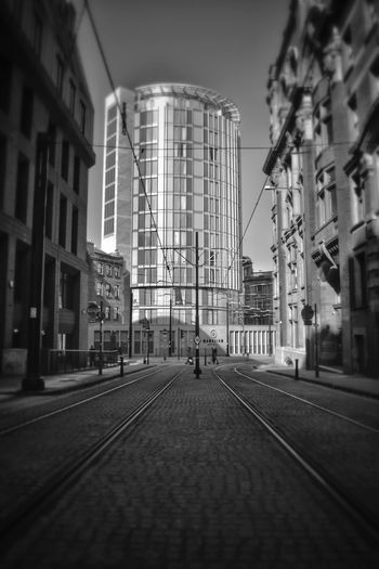 one of the l streets in the city centre of Manchester Malephotographerofthemonth Blackandwhite Photography Bnw monochrome photography Streetphotography Manchester UK City Skyscraper Sky Architecture Building Exterior Built Structure Railroad Track vanishing point Rail Transportation Diminishing Perspective The Way Forward Empty Road Cityscape