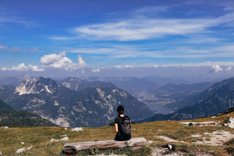 Man sitting on mountain against sky