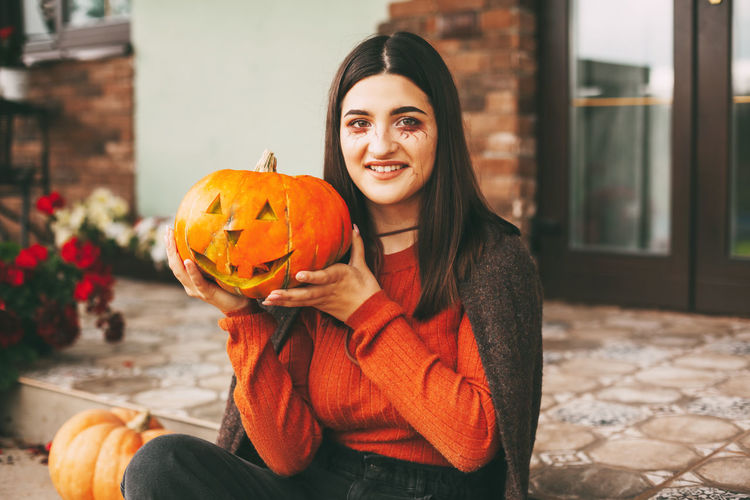 Portrait of a smiling young woman holding pumpkin outdoors