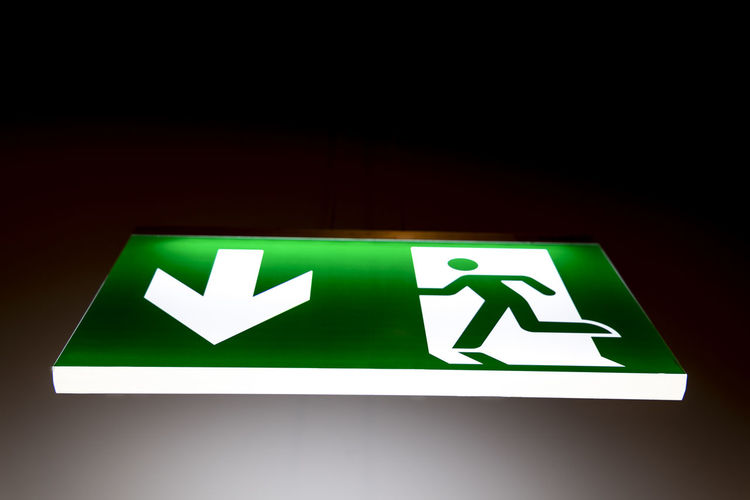 Illuminated Exit Sign. Arrow Symbol Below Black Background Close-up Communication Direction Directional Sign Directly Below Emergency Exit Exit Sign Green Color Guidance Human Representation Illuminated Illuminated Signs Indoors  Information Information Sign Leaving No People Representation Safety Sign Symbol Urgency