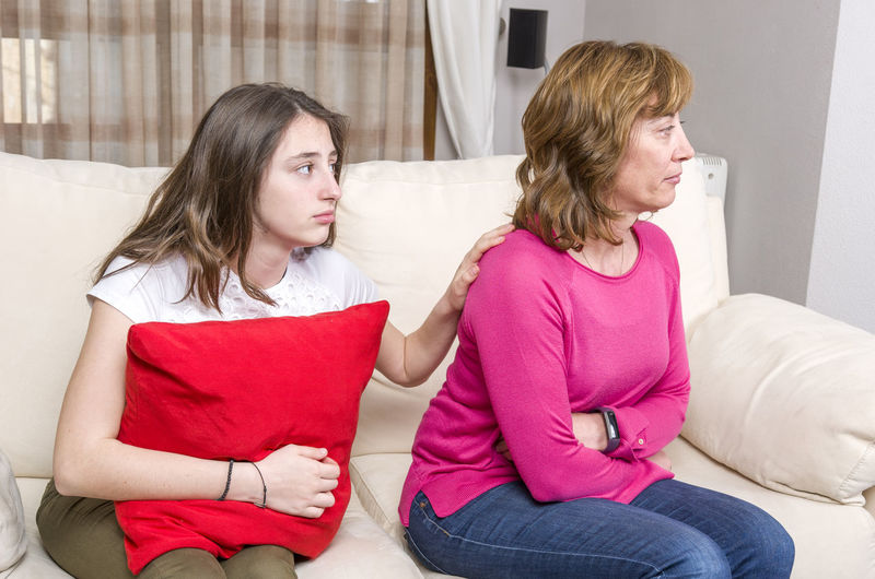 Daughter holding cushion comforting angry mother on sofa at home