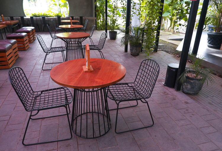 Empty chairs and table against building