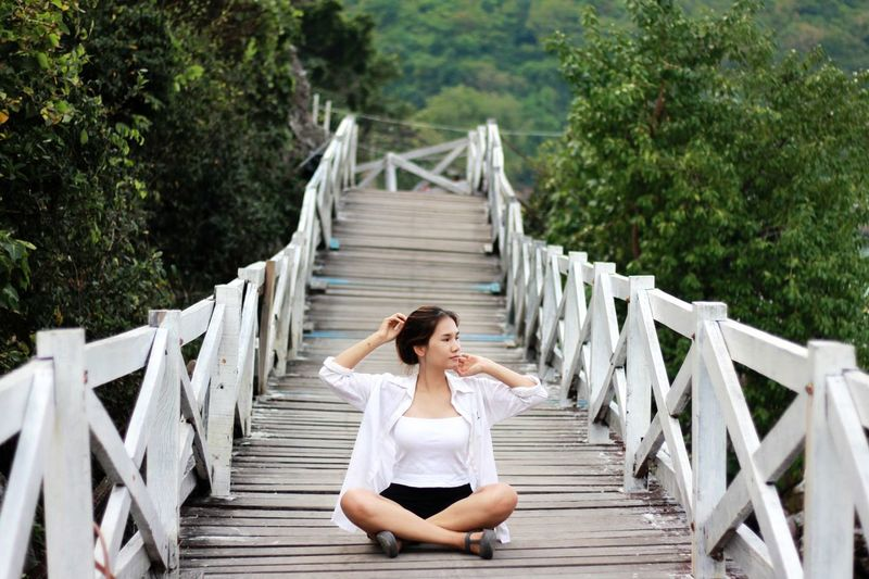 Woman sitting on footbridge against trees