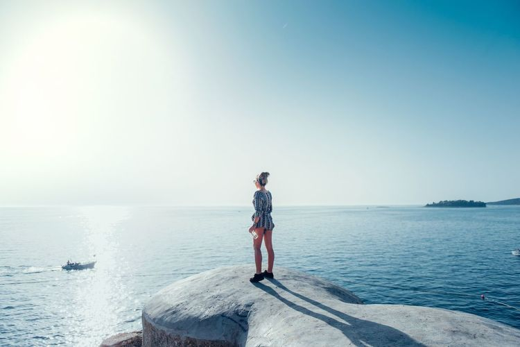 Woman Standing On Coast Against Clear Sky