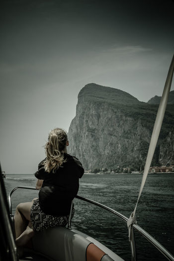 Rear view of woman looking at sea while sitting on boat against mountain