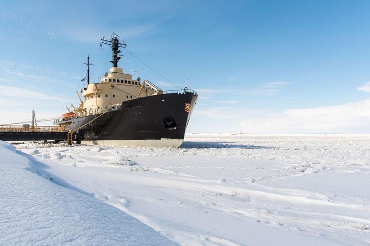 Frozen boat in winter against sky