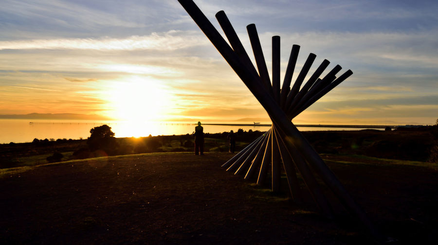 Sunset At Oyster Bay Pt. 9 Rising Wave Sculpture 16 Poles Sculptor : Roger Berry Stainless Steel Sculpture Oyster Bay Regional Park San Francisco Bay Sunset Silhouettes Sundown Sunset Sunset Collection Sun's Glow Glare Marin Headlands Pier Final Approach To Oakland Airport Airplane Landing Spectacular Views Landscape_Collection Hilltop Man Watching Sunset All About Angles Horizon Over Water Tree Silhouette Cloud - Sky Dramatic Sky Tranquility Shore Scenics