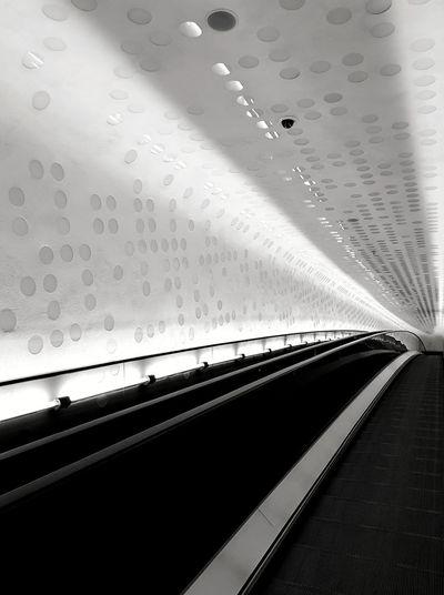 Interior of illuminated railroad station seen through window