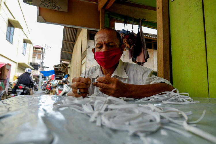 Low angle view of man wearing mask holding textiles on table