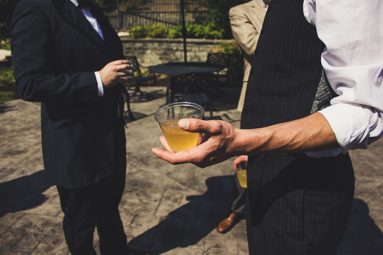 Midsection of men holding drink in glass while standing outdoors