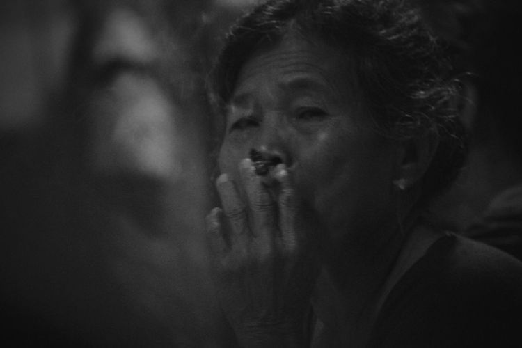 Portrait of mature woman smoking cigarette at night