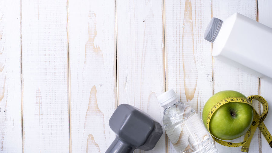 Close-up of exercise equipment with granny smith apple on table
