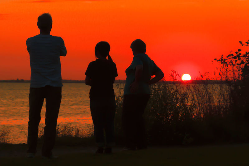 Beauty In Nature Field Friendship Group Of People Land Leisure Activity Lifestyles Men Nature Orange Color Outdoors People Real People Rear View Silhouette Sky Standing Sunset Three Quarter Length Togetherness