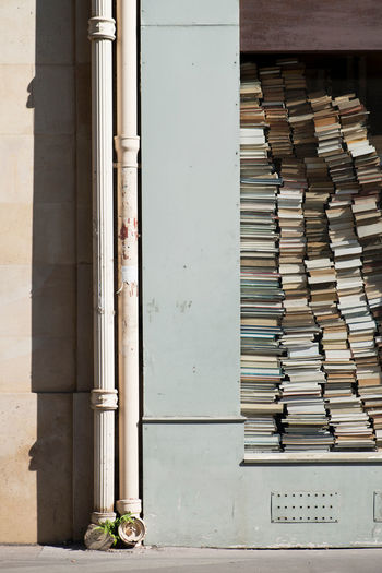 Stack of books on shelf against building