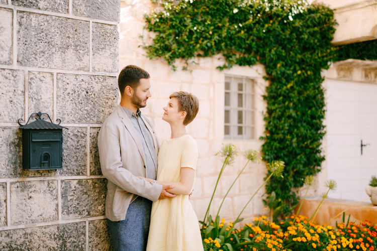 Young couple standing by wall outdoors