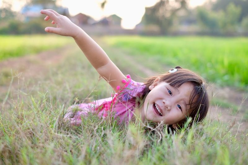 The little girl is lying on grass and the evening sun light Lying Down Playing Field Sunlight Kids Portrait One Person Plant Field Childhood Grass Child Looking At Camera Smiling Headshot Leisure Activity Land Females Happiness Arms Raised Hair Girls Women Nature Day