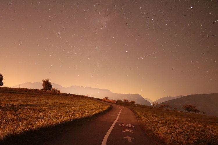 Road amidst field against sky at night