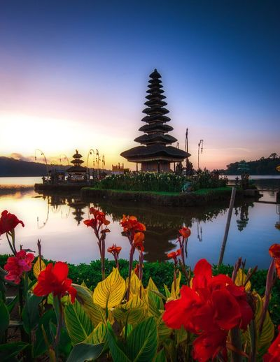 View of temple at lake during sunset
