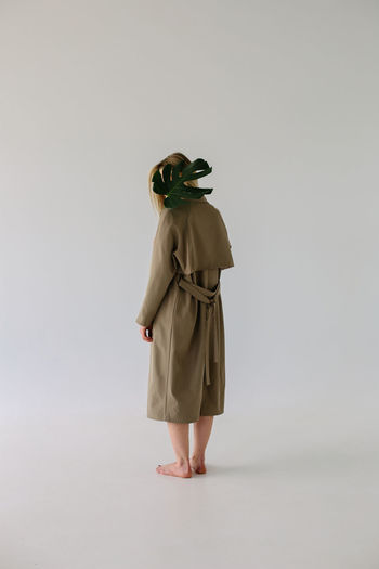 Studio Shot Women Copy Space Hairstyle Obscured Face Casual Clothing Real People Clothing Lifestyles Rear View Leisure Activity Full Length Indoors  Standing Gray Adult White Background One Person Fashion Cut Out Plant Leaf Monstera Hiding Trench Coat Fashion Young Women Young Adult Girls Females Minimalist Side View