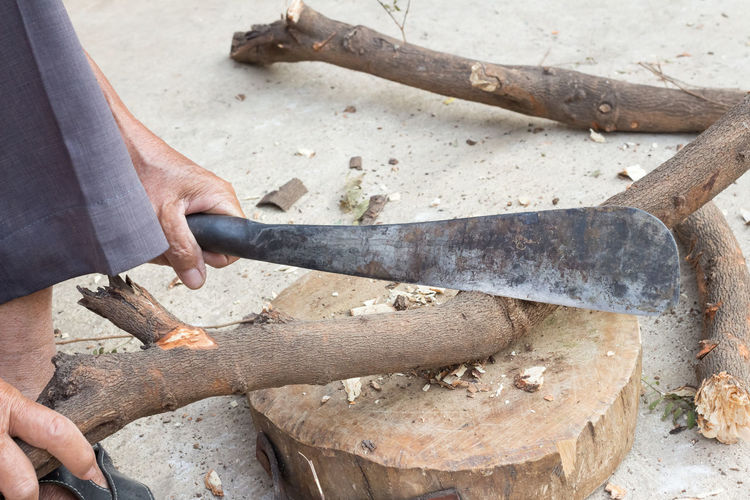 Low section of man cutting wood