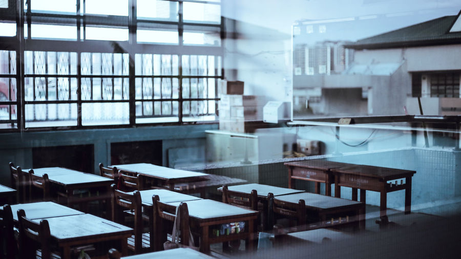 Empty chairs and tables in building seen through glass window
