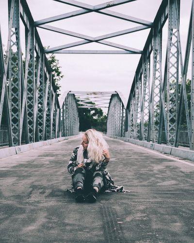People sitting on bridge against sky