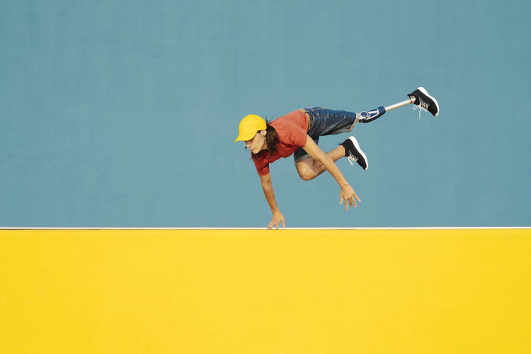 Low angle view of man jumping against yellow wall
