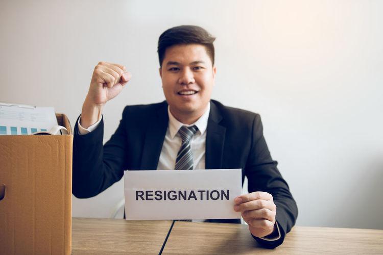 Portrait of smiling businessman holding resignation letter at desk in office