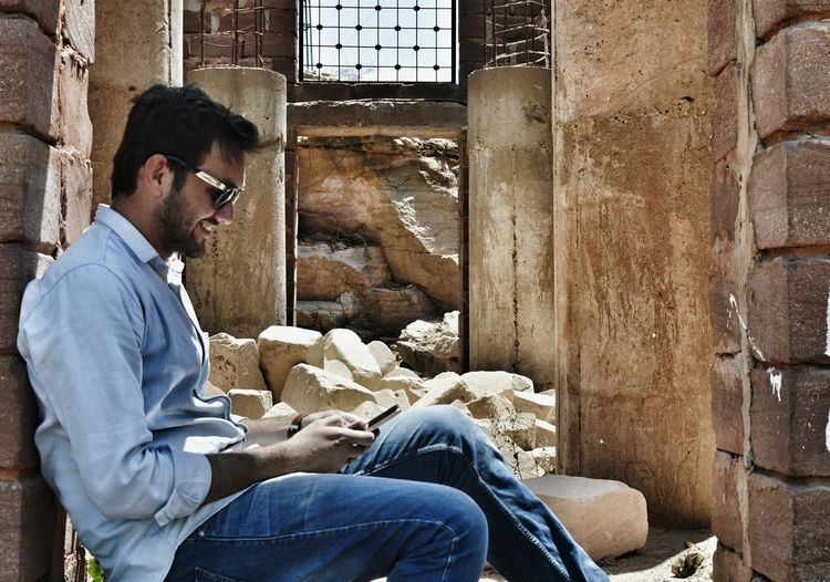 Side view of young man using smart phone while sitting at ruins