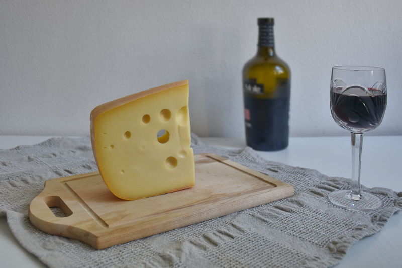 Close-up of wine and cheese served on table