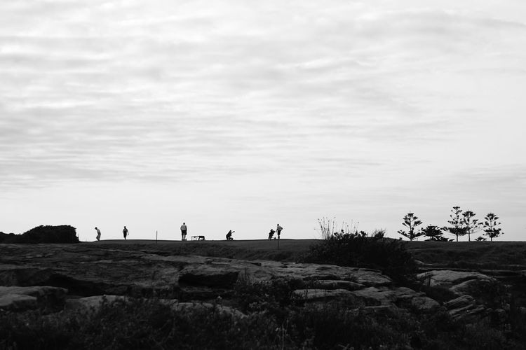 Mid distance of people on landscape against sky