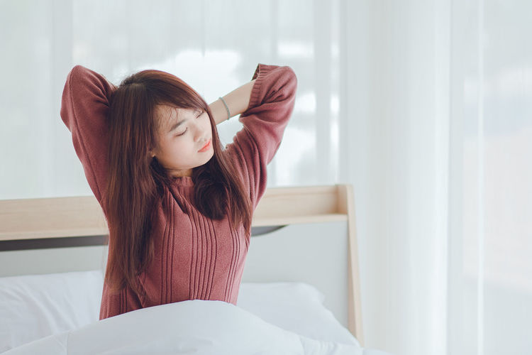 Woman waking up on bed at home