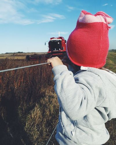 Close-up of kid wearing warm clothing while looking at combine harvester