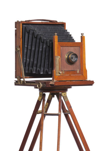 Antique wooden camera on tripod isolated on white White Background Cut Out Wood - Material Single Object Camera - Photographic Equipment Old Camera Antique Vintage Isolated Lens - Optical Instrument Tripod Bellows Large Format Shutter Brass Glass - Material No People 1880s 1890s Knob Handle Black Brown Color Image
