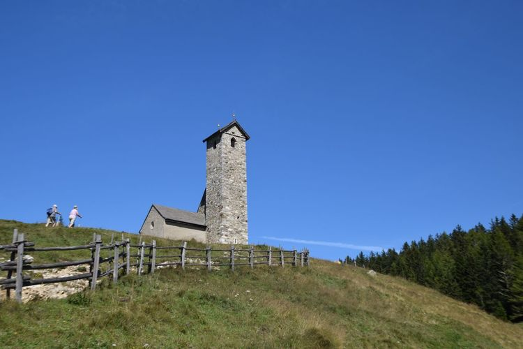 Low angle view of chapel on hill against clear blue sky