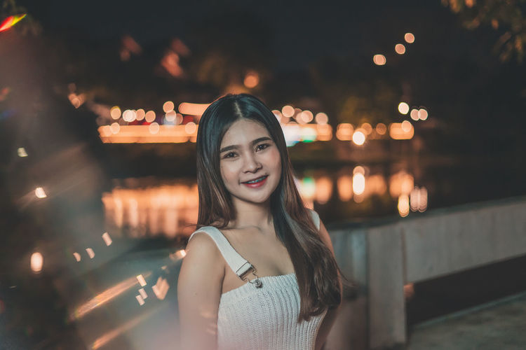 Portrait of smiling young woman standing on bridge over river at night