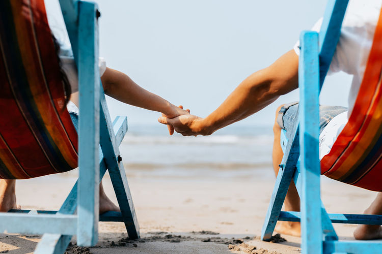Cropped image of couple holding hands while relaxing on chair at beach