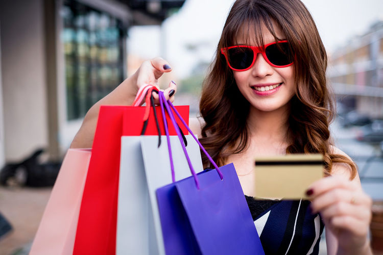 Close-Up Of Young Woman Holding Shopping Bags With Credit Card In City