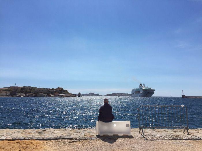 Rear View Of Man Sitting At Shore Looking At View