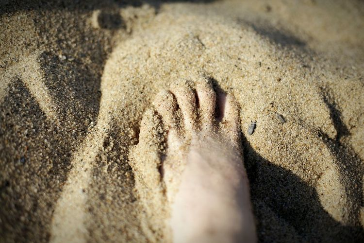 Cropped image of foot amidst sand at beach