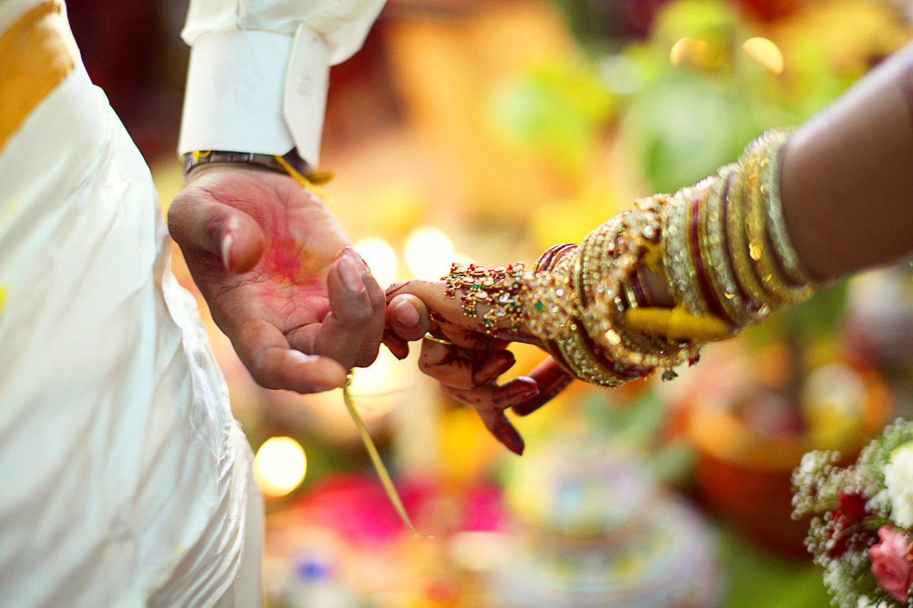 Cropped hand of couple holding hands during wedding