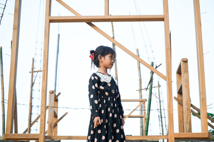 A little asian girl is angry in front of a house building