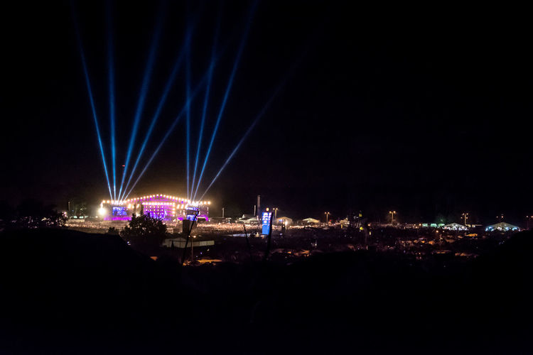 Spotlight Festival Concert Stage Arts Culture And Entertainment Illuminated Lighting Equipment Light Event Nightlife City Copy Space Architecture Light - Natural Phenomenon No People Dark Light Beam Cityscape Building Exterior Nature Outdoors Glowing Built Structure Laser Music Festival