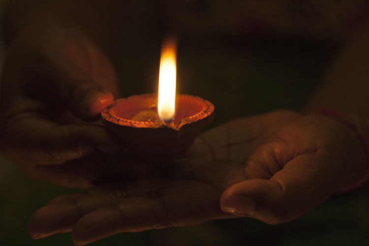 Cropped Hands Holding Illuminated Diya In Darkroom