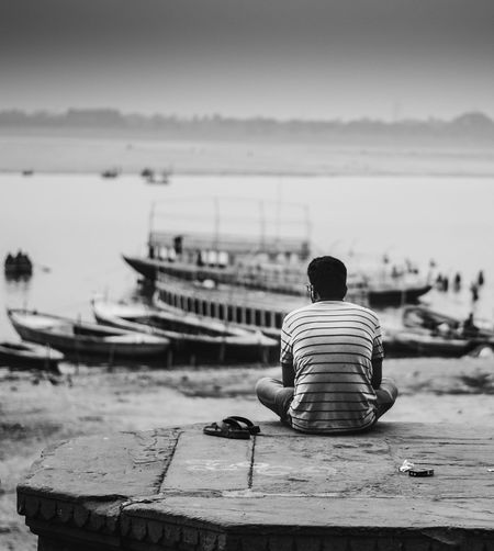 Rear view of man sitting on pier with boats in background