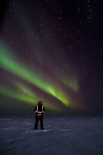 Full Length Of Man Standing On Snow Covered Landscape Against Aurora Borealis
